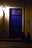 Stoop Sitting: Sometimes the scale of things can make the ordinary seem, well, out of it. The size of the lamp and the door with the two regular size girls in deep conversation on a dark night intrigued me.