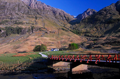 Whitewashed cottage and red bridge below the towering mountains - Glencoe, Scotland