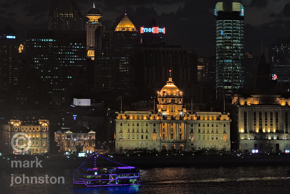 An illuminated river cruise boat passes along the Huangpu River in central Shanghai.  Buildings along the waterfront include [from left]: The Great Northern Telegraph Building, The China Merchants Company Building, the domed Hong Kong and Shanghai Banking Corporation [HSBC] Building, and the Shanghai Customs House.