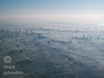 I got this remarkable shot shortly after take-off from Shanghai's Hongqiao airport, which serves a lot of the domestic air traffic in and out of Shanghai.  A combination of still air, clouds, and city smog gives makes for a surreal and ghostly cityscape.