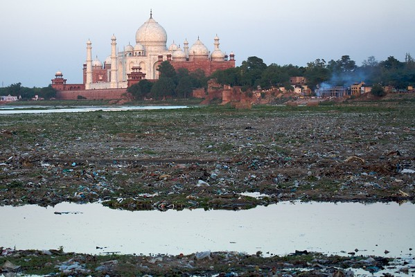 The contrast between beauty and ugliness is clearly seen as one looks at the Taj Mahal from the banks of the Yamuna River.