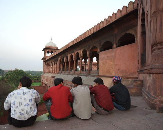 A group of guys sit outside Jama Masjid Mosque at sunset.
