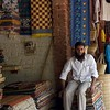 Carpet vendor relaxes in the midday heat<br /> , Dali Haat Market, Delhi.
