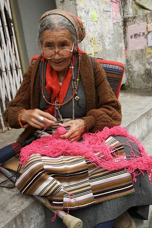 An old woman knitting on the side of the road.