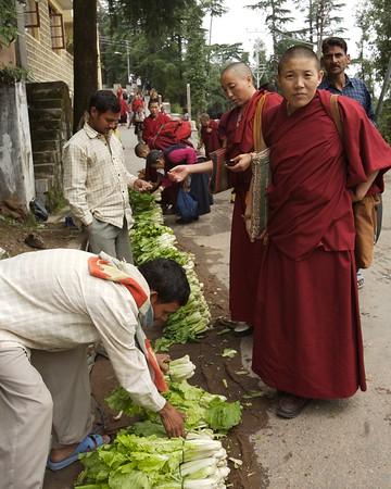 Buddhist monks buying fresh vegetables.