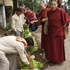 Buddhist monks buying fresh vegetables.