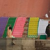Women set colorful blankets on the steps to dry after washing them in the Ganges.