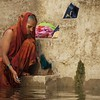 A woman washes clothes in the Ganges.