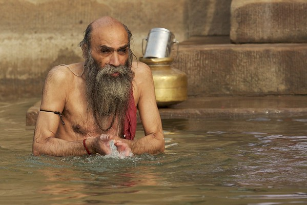 This man chants prayers as he splashes himself with water.