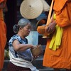 Most people kneel and say prayers as they give their offerings to the monks.