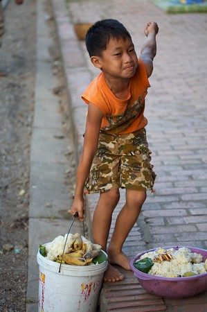A young boy tries to lift the heavy bucket of leftover offerings.
