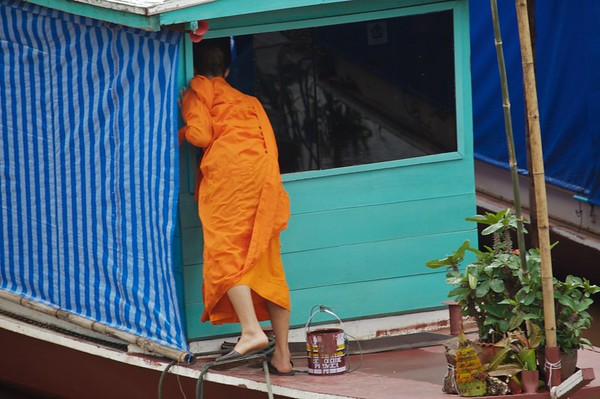 A monk looks inside a riverboat in the early morning hours.