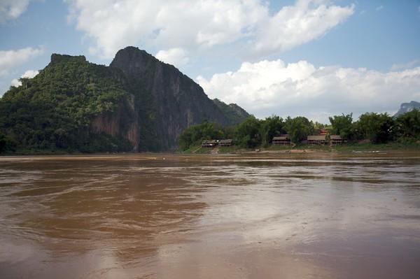 Riverside village surrounded by mountains near Luang Prabang.