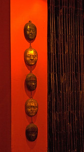 Metal masks on a red wall inside the Red Piano restaurant-The Red Piano Restaurant-Cambodia