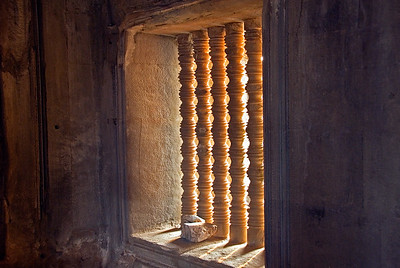 Stone window with columns with light from setting sun-Angkor Wat-Cambodia