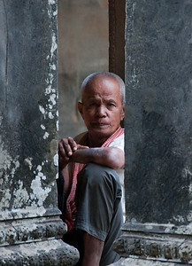 Head-on view of Cambodian man flanked by stone columns sitting inside gallery-Angkor Wat-Cambodia