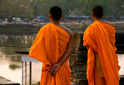 Buddhist monks in saffron robes looking across relfecting pool-Angkor Wat-Cambodia