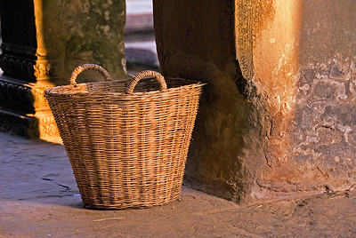 Large basket inside gallery beside worn stone column-Angkor Wat-Cambodia