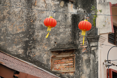 Red lanterns hung in preparation for Chinese New Year celebrations with mold covered building wall in background-Chinese Settlement-Melaka-Malacca Town-Malaysia