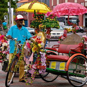 Flower covered pedicabs with red and yellow umbrellas-Street Scene-Melaka-Malacca Town-Malaysia