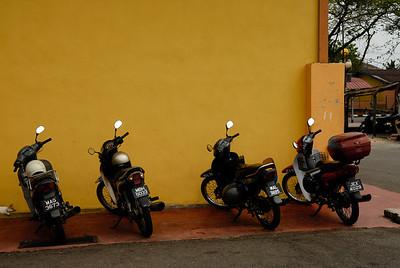 Motor cycles parked beside yellow wall-Market-Melaka-Malaysia