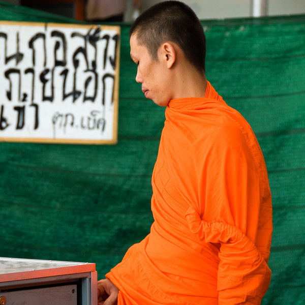Buddhist monk in saffron robes on sidewalk-Grand Palace-Bangkok-Thailand
