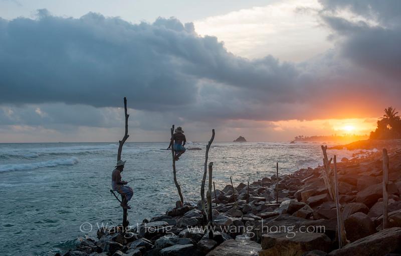 Stilt fishermen at sunset on Koggala Beach.