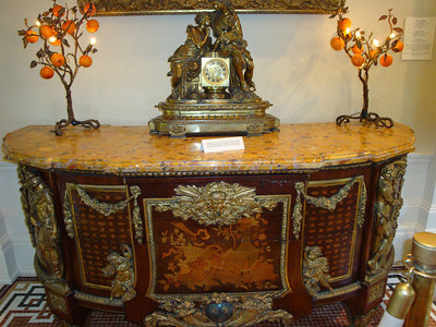 An old dresser with mantle clock in the lobby of the Lightner Museum.