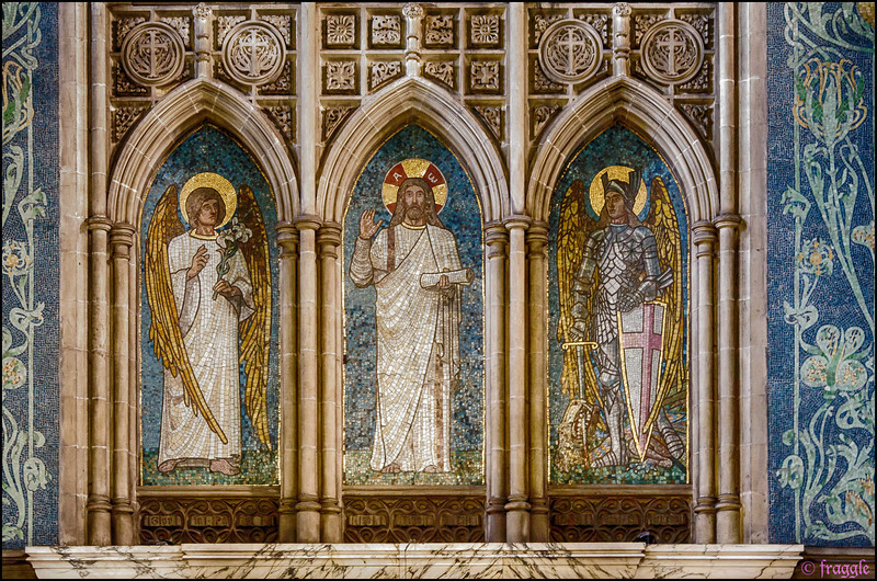 Above the altar are three mosaic figures, to the design of Charles William Mitchell. In the centre is a figure of the risen Christ with the Greek letters A and Ω - Alpha and Omega, the beginning and the end. To the left of the central figure stands St Gabriel the Messenger and to the right St Michael the Archangel.