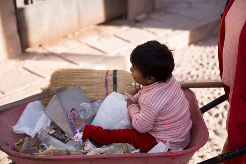 Some kids get carried in knapsacks or bundles; some get wheeled around in a wheel-barrow!