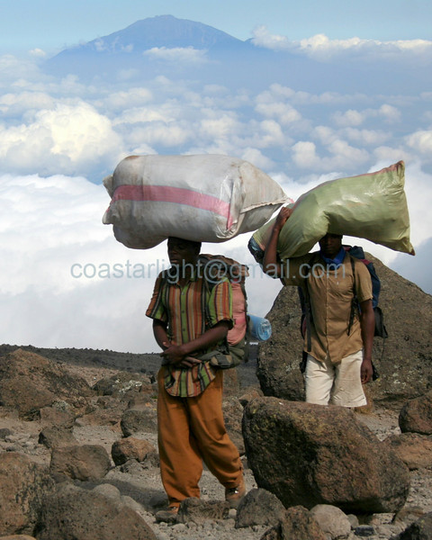 Porters, Mount Meru in background