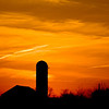 beautiful sunset on the farm with barn and grain silo silhouette