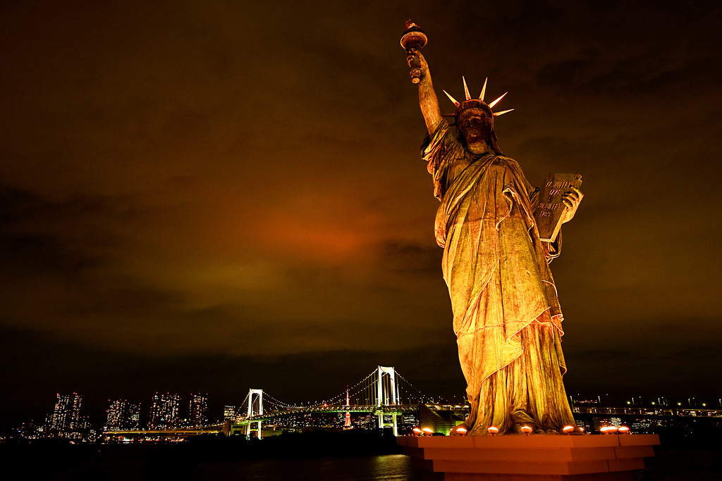 East & West<br /> <br /> While looking for a spot to shoot the Rainbow Bridge, I ran into this Statue of Liberty replica in Odaiba, Tokyo. The tokyo tower fully iluminates the cloud covered sky and can be seen between the bridge's towers.<br /> <br /> Nikkor 16-35 @ f8