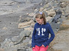 My daughter hurries down the rocks to the sand.