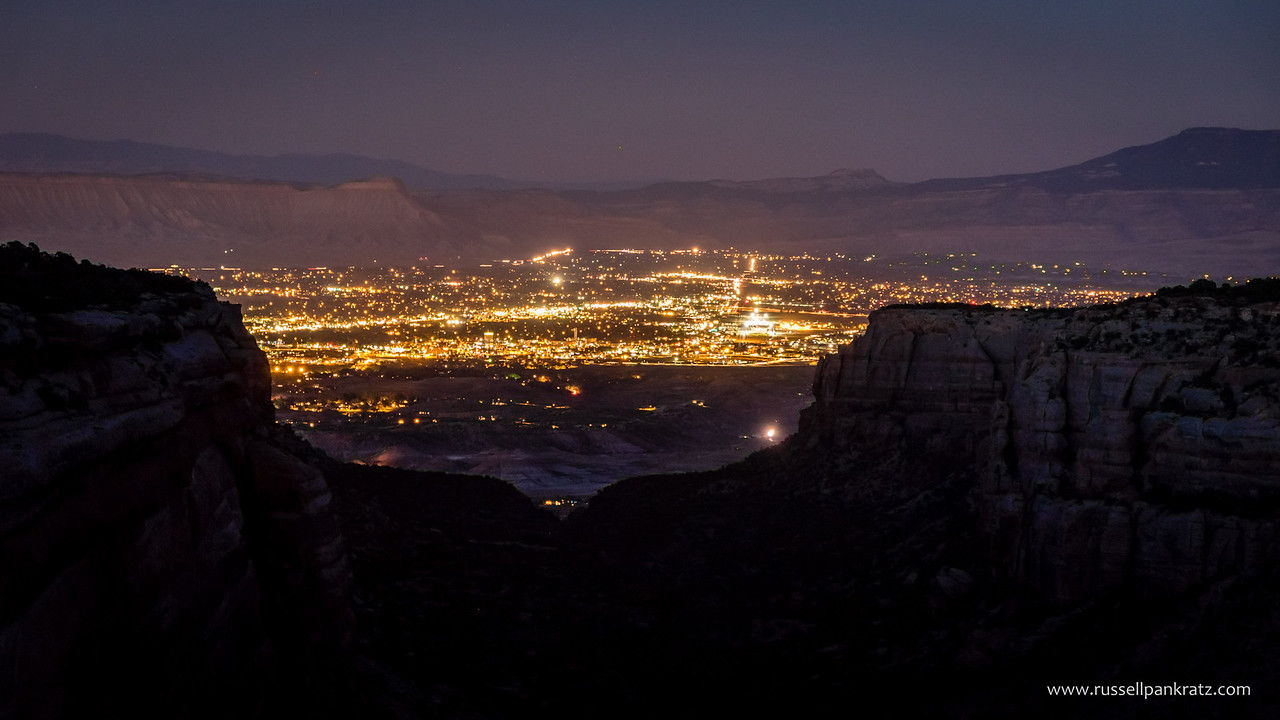The view of Grand Junction, Clifton, and Palisade, CO from Rim Rock Drive in The Colorado Monument. Beyond, and illuminated by the city lights is the Bookcliffs Mountain Range on the left and the Grand Mesa to the right.
