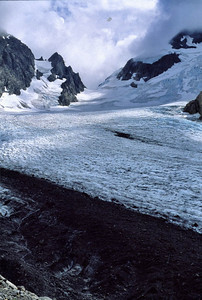 A glacier is to a mountain, what a belt sander is to balsa wood. It is a ferocious erosive force. The shear mass of the glacier causes the physical characteristics of the ice to behave as a plastic. Under pressure, it deforms and molds itself around rocks that lie beneath the glacier and along its sides. The weight of the ice causes it to actually flow down the face of the mountain plucking rocks from that face as it moves, gauging a valley as it goes.  That dark swath of rock in the bottom third of the image is actually a relatively thin venier of rock and gravel on top of the glacier. The rocks have been eroded from the face of Mt. Mathias on the left. They are then transported, conveyor-belt style down the valley and deposited, as the ice melts, along the sides and the terminus of the glacier in lateral and terminal morraines.