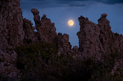 The moon rises behind the south tufas at sunset - Mono Lake, California.