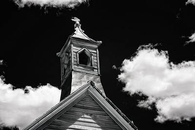 An infrared photo of the cupola, with a gull perched on top, of the Methodist Church in Bodie State Park, California.