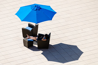 Browsing with a tablet under a blue patio umbrella.