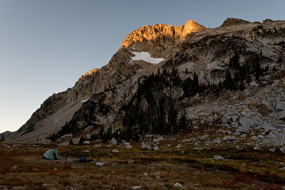 Morning sunlight capping the mountains looming over my campsite.