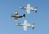 Two A10 Warthogs flying with a WII vintage fighter bomber.