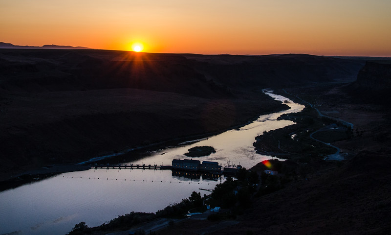 The sun just touching the horizon above the Swan Falls Dam on the Snake River.