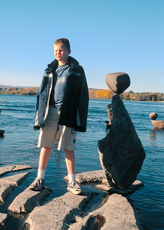 Jacob petulantly posing by ephemeral Ottawa River rock sculptures. The Ottawa River rock sculptures are not meant to last. River ice, floods and vandalism constantly overturn the stones leaving the artist with a Sisyphean restacking task; it's Buddha's everything changes manifested in obdurate stone.