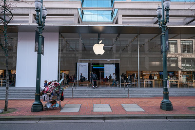 Contrast between rich and poor- homeless shopping cart parked in front of Apple Store