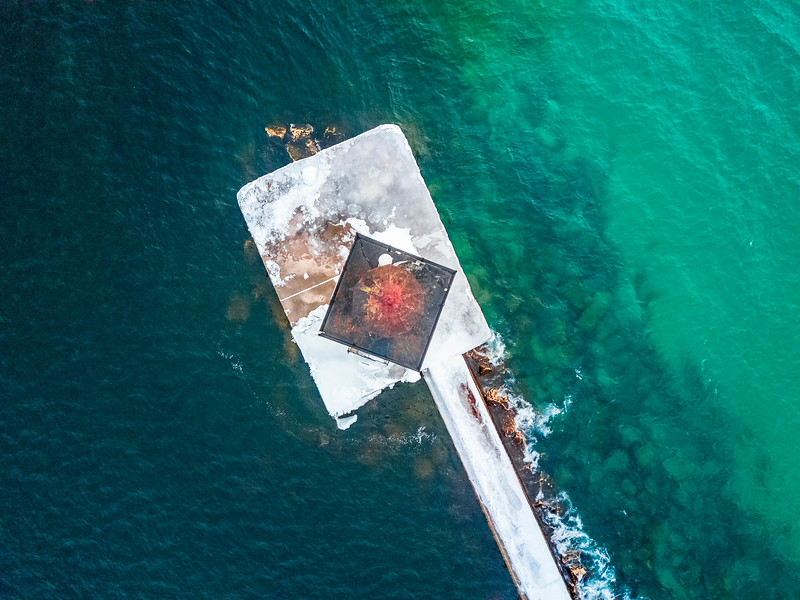 Top down aerial view of the Frankfort North Breakwater Light showing the color change of the Lake Michigan (right, light) and Frankfort Harbor (left, dark) water - March 14th, 2017
