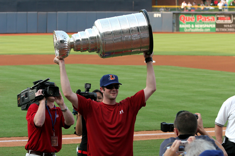 Playoff MVP Cam Ward of the Carolina Hurricanes lifts the Stanley Cup for fans at a Durham Bulls baseball game - Durham