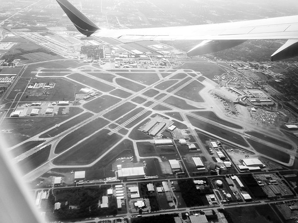 Black and white aerial photo looking down on the William P. Hobby Houston Airport (HOU)  from the back row window seat after we turned crosswind, downwind, and departed the pattern.
