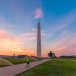 A runner jogs toward the Washington Monument at sunrise in Washington D.C.
