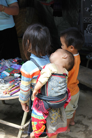 Hmong girl carrying baby brother
