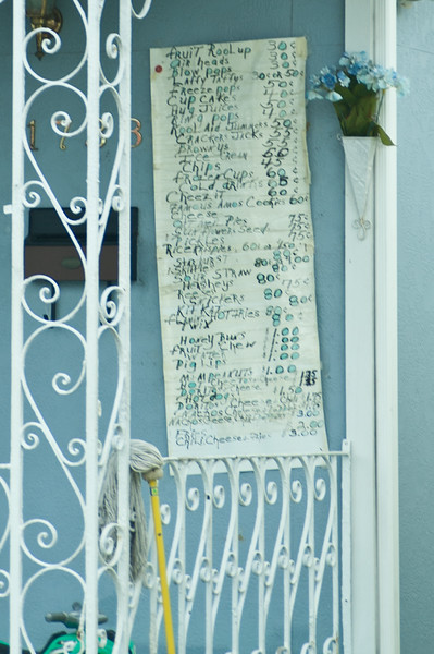 A menu of items for sale on the front porch of a home in NOLA